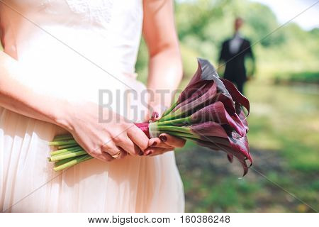 Wedding Bouquet Of  Calla. Bouquet Of Purple Flowers. Beautiful Wedding Bouquet In The Bride's Hands