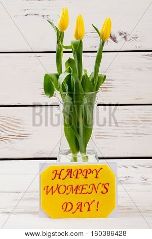 Women's Day card and tulips. Flowers in vase near card. Make nice surprise for wife. Handmade spring gift.