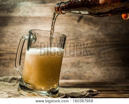 Foamy beer from bottle poured into mug standing on empty wooden background