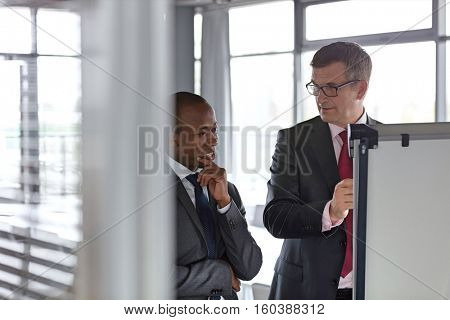 Mature businessman looking at male colleague while writing on whiteboard in office