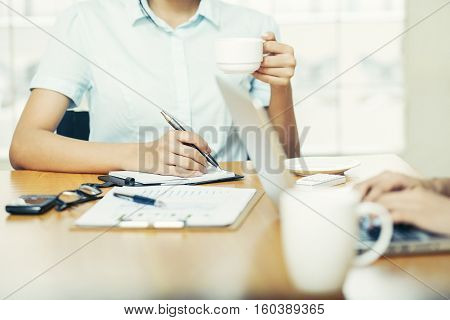 Woman hand writing on her notepad and holding coffee cub
