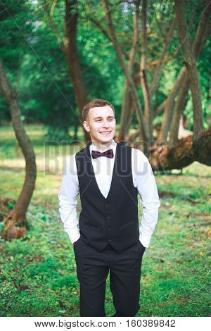 Groom on his wedding day.Gorgeous smiling groom. andsome groom at wedding tuxedo smiling and waiting for bride.Elegant groom in black costume and bow-tie. Groom in a suit holding buttonhole.