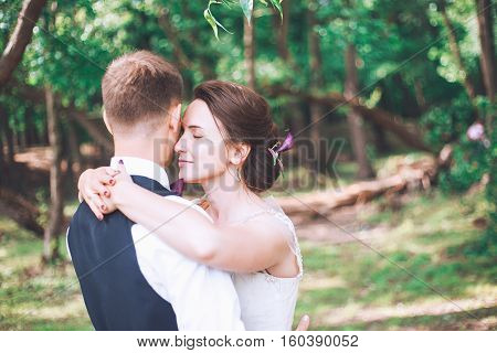 Groom and bride together. couple hugging. Wedding day. Beautiful bride and elegant groom walking after wedding ceremony. Luxury bridal dress and bouquet of flowers. Bride and groom at wedding day