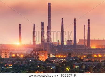 City Buildings On The Background Of Steel Factory At Sunset