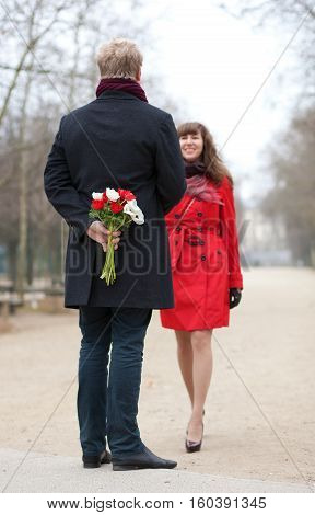 Happy Couple Having A Date, Man Is Going To Offer Flowers To His Girlfriend