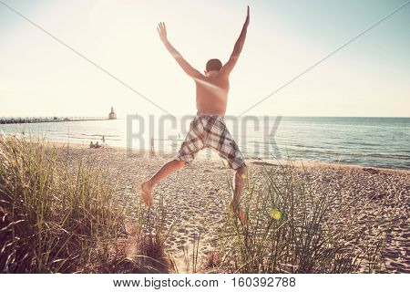 Boy jumping off of dunes at the beach.