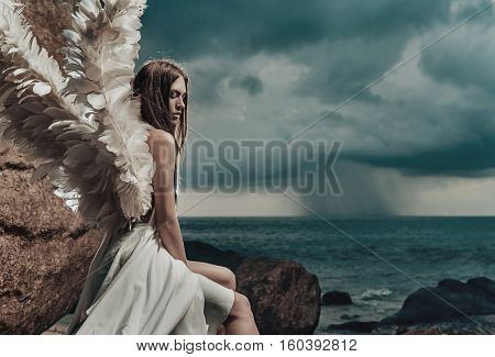 Fine art photo of a woman in white dress as an angel