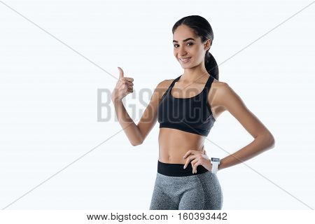 Super. Beautiful woman holding left hand on the waist keeping right thumb upwards while standing in semi position over white background