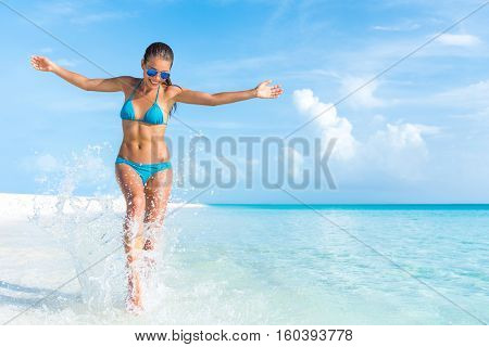 Sexy bikini body woman playful on paradise tropical beach having fun playing splashing water in freedom with open arms. Beautiful fit body girl on luxury travel vacation.