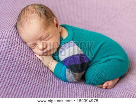 cute newborn baby in warm overalls sleeping on blanket