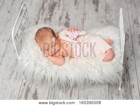 newborn sleeping baby in panties holding toy on cute little bed with white fluffy blanket