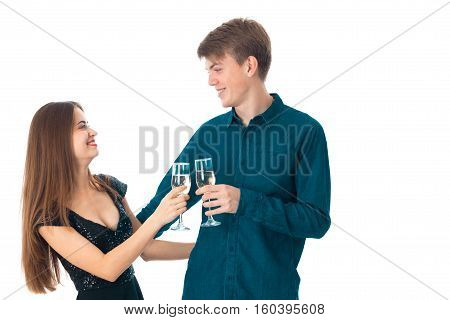 attractive young couple in love with two glasses of champagne in studio on white background