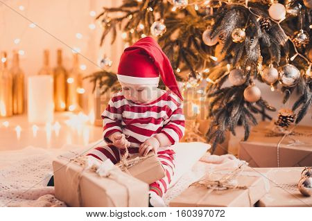 Cute baby girl 1 year old open Christmas presents sitting on floor under Christmas tree in room. Holiday season.
