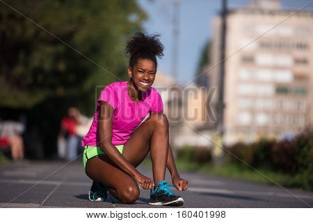 African american woman runner tightening shoe lace - Fitness, people and healthy lifestyle