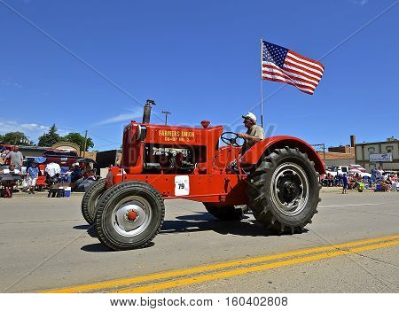 MANDAN, NORTH DAKOTA, July 3, 2016: The 4th of July Rodeo Days  3 day celebration includes the rodeo, Art in the Park, and downtown 4th parade where this Farmers Union Co-op #3 restored tractor is featured.