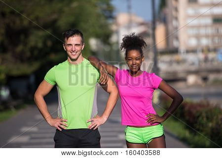 portrait of young multietnic jogging couple ready to run on fresh morning in the city