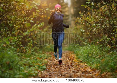 Blond girl running among trees