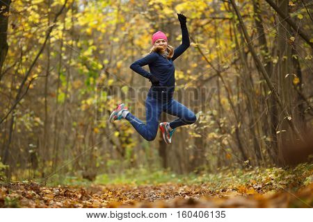 Sportswoman running among autumn leaves