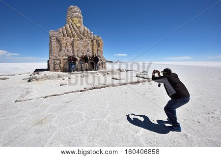 UYUNI BOLIVIA - AUGUST 28 2016: Unidentified people at Dakar Rally Monument in Salar de Uyuni (Salt Lake) near Uyuni Bolivia.
