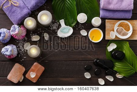 Spa treatment tools and aromatherapy concept background. Zen stones, aroma salt, spices, herbal balls, oil and soap, candle and details of wellness body care and alternative indian medicine, top view