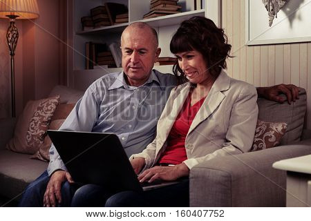 Side mid shot of man in shirt and woman in red blouse and blazer looking at laptop. A booksettle behind them, a lamp on their right