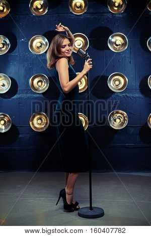 Side full-length shot of a pretty woman singing into the microphone over background with spotlights. Set of well-chosen dress and accessories