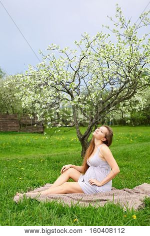 Beautiful pregnant woman in blooming spring garden