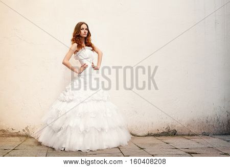 Beautiful young bride posing against a background of an old wall