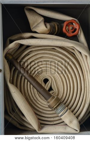 Historic rolled up fire hose with spray nozzle - close up