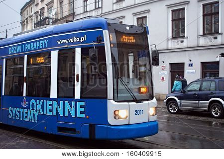 POLAND KRAKOW - JANUARY 01 2015: Tram Bombardier Flexity Classic in the historic part of Krakow in winter. Total in Krakow more than 90 kilometers of tram tracks and 24 routes.