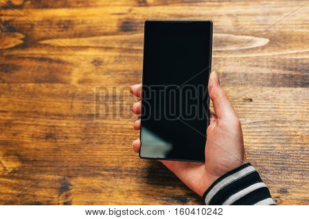 Mobile payment and electronic banking female hand with elegant new black smartphone and blank screen as copy space