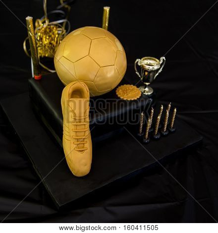 Chocolate birthday cake with football and shoe decoration