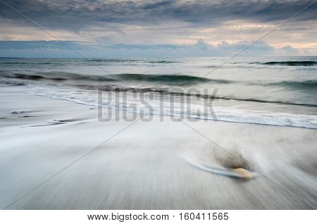 Pebbles on the beach on a black sand and flowing sea water during sunset creating nice textures. Long exposure image.