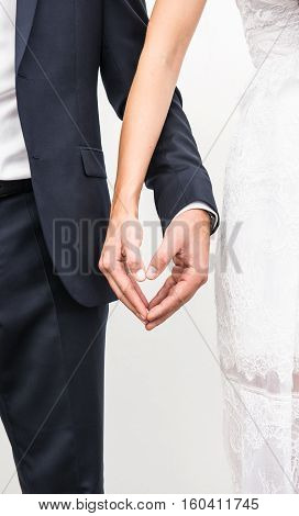 Just married couple holding hands and making heart shape with fingers