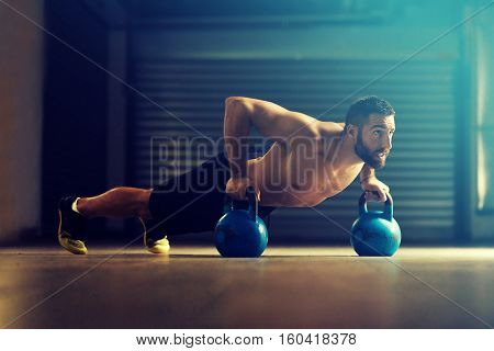 Young fitness man is training by kettlebell.
