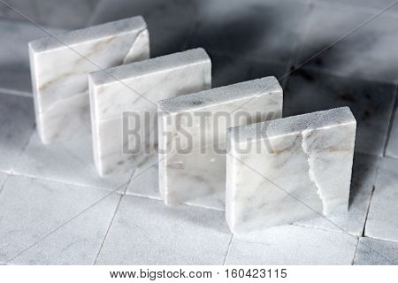 Detail of four small square tiles of white Carrara marble. Tuscany Italy