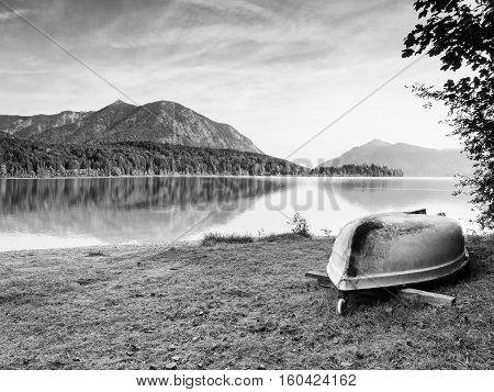 Upside Down  Fishing Paddle Boat On Bank Of Alps Lake. Morning Autumnal Lake.