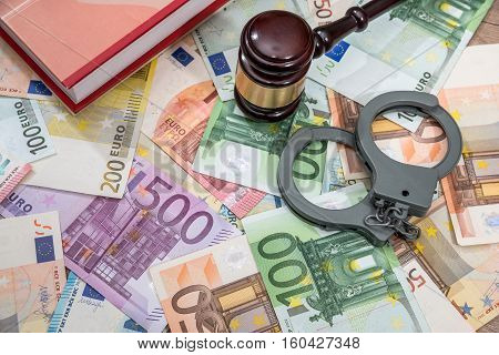 handcuffs with hammer of judge and euro. business concept