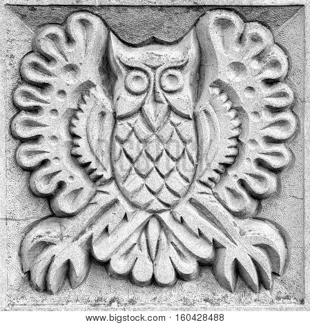 fabulous big owl a stone bas-relief on the wall