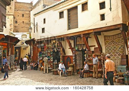 FEZ MOROCCO - MAY 19 2006: Shop keepers and their shops selling ceramic plates and other goods to tourists at the ancient medina Fes el Bali in Fez Morocco.