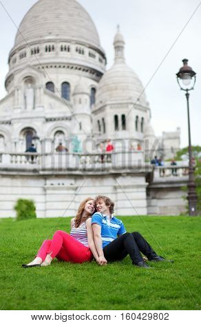 Couple Of Tourists Sitting On The Grass By The Sacre-coeur