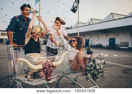 Multiethnic young people racing with shopping cart. Young friends having fun on a shopping carts and confetti.