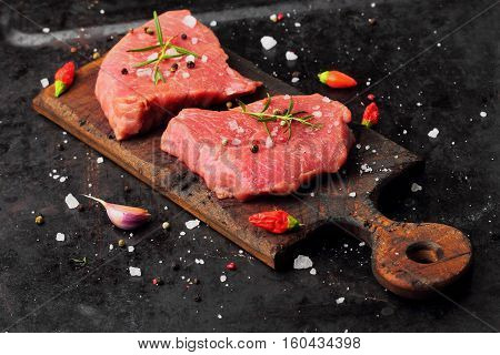 Fresh Raw Beef Steak Mignon, With Salt, Peppercorns, Rosemary, Pepepr Chili.on Dark Table.copy Space