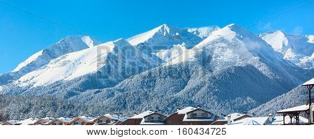 Winter travel vacation nature panoramic background with snow covered mountain peaks and snow roofs, Pirin, Bulgaria