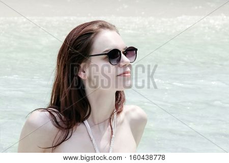 pretty white girl with sunglasses sitting on beach