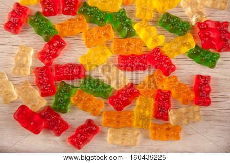 Heap of mixed multicolored red green orange yellow gelatin sweets on light background