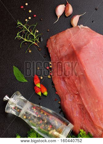 Fresh And Raw Meat With Black Red Pepper And Rosemary And Garlic. Whole Piece Of Red Meat Ready To C