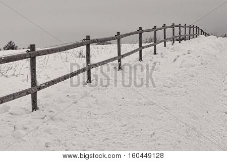 Black and white shot of a fence in the snow on a gray day