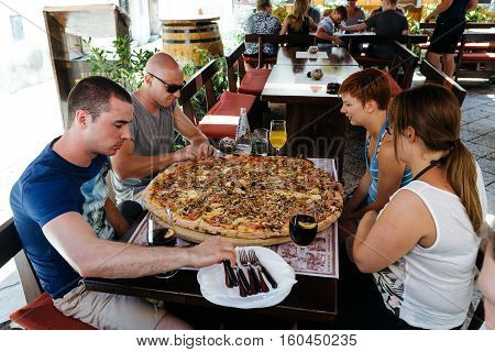Porec, Croatia - July, 2016 - Group of people eat a large pizza at the legendary stari saloon.