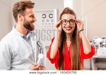 Young and happy female patient trying new eye glasses with ophthalmologist in the cabinet